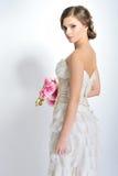Amincissez la belle femme avec des fleurs portant les dres luxueux de mariage Image libre de droits