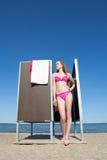 Amincissez la belle femme dans le vestiaire sur la plage Photo stock