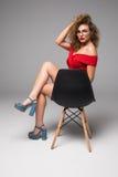Amincissez la belle femme posant sur une chaise noire dans les sous-vêtements sexy sur le fond gris Photos libres de droits