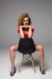 Amincissez la belle femme posant sur une chaise noire dans les sous-vêtements sexy sur le fond gris Image stock