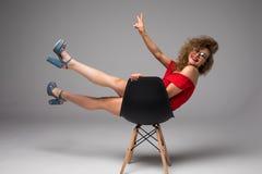 Amincissez la belle femme posant sur une chaise noire dans les sous-vêtements sexy sur le fond gris Photo libre de droits