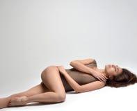 Amincissez la belle femme se trouvant sur un plancher dans les sous-vêtements sexy sur le gris Photos stock