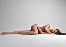 Amincissez la belle femme se trouvant sur un plancher dans les sous-vêtements sexy sur le gris Images stock