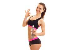 Amincissez la belle fille dans le dessus et les shorts de sports tenant une bouteille de l'eau dans sa main et geste correct d'ex Photos stock