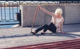 Amincissez la femme agée essayant de se lever du trottoir Photo libre de droits