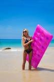 Amincissez la femme blonde avec le matelas rose de natation sur la plage tropicale Image stock