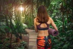 Amincissez la femme caucasienne avec le tapis de yoga à la serre chaude Images libres de droits