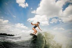 Amincissez la femme de sourire wakesurfing sur le conseil contre le ciel Photos stock