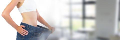 Amincissez la femme en bonne santé tenant des jeans s'adaptant par la fenêtre Image stock