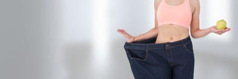 Amincissez la femme en bonne santé tenant l'ajustement de pomme et de pantalons Photos stock