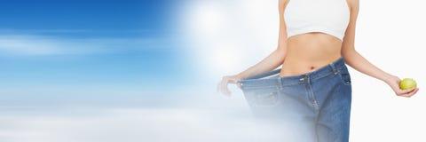 Amincissez la femme en bonne santé tenant la pomme et tirant l'ajustement de pantalons Photographie stock libre de droits