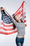 Amincissez la femme gaie se soulevant vers le haut du drapeau des USA derrière elle de retour Images stock