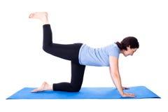 Amincissez la femme mûre faisant des exercices sur le tapis de yoga d'isolement sur le blanc Photos stock