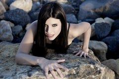 Amincissez la femme magnifique convenable regardant sur des roches Images stock