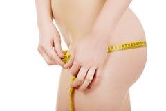 Amincissez la femme mesurant ses gratte-culs Images stock