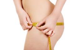 Amincissez la femme mesurant ses gratte-culs Photos libres de droits