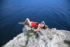 Amincissez la femme sexy se trouvant sur le bord de la roche Photos stock
