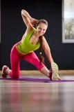 Amincissez la femme sportive établissant dans le gymnase faisant l'exercice ou les mouvements brusques de genou-rebond Photos libres de droits