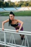 Amincissez la femme sportive avec des haltères dans le stade Photos stock