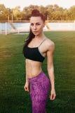 Amincissez la femme sportive avec des haltères dans le stade Photographie stock