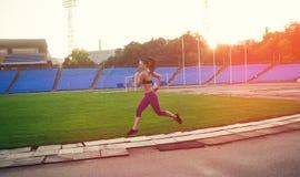 Amincissez la femme sportive avec des haltères dans le stade Photos libres de droits