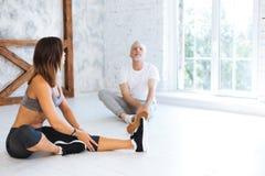 Amincissez la femme sportive montrant des exercices à son visiteur Photo libre de droits
