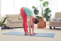 Amincissez la fille attirante s'étirant sur le compagnon de yoga dans le salon Photo libre de droits