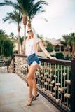 Amincissez la fille bronzée avec l'extérieur debout de longs cheveux près de la piscine et le regard par des lunettes de soleil Photographie stock