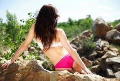Amincissez la fille sportive s'asseyant sur les roches et regardez loin Photo libre de droits