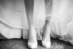Amincissez la jambe de la jeune mariée sensible dans des chaussures blanches sous une robe de mariage Photographie stock libre de droits