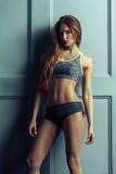 Amincissez la jeune fille bronzée de sports sur le fond foncé de mur Images stock