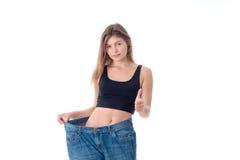 Amincissez la jeune fille dans de grands jeans d'isolement sur le fond blanc Photos stock