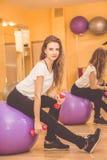 Amincissez la jolie femme avec le fitball pourpre dans le gymnase Image libre de droits