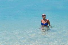 Amincissez la natation blonde de femme dans l'eau claire sur la plage tropicale Photos libres de droits