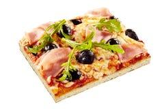 Amincissez la pizza italienne avec les olives, la fusée et le jambon Photographie stock libre de droits