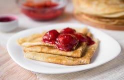 Amincissez la triangle pliée par crêpes russes avec de la sauce à fraise d'un plat blanc Photo stock
