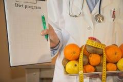 Amincissez le concept suivant un régime vers le bas Docteur dans le manteau blanc de laboratoire recommandant la nourriture saine Photographie stock