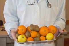 Amincissez le concept suivant un régime vers le bas Docteur dans le manteau blanc de laboratoire recommandant la nourriture saine Photos stock