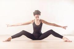 Amincissez le jeune danseur classique faisant en étirant l'exercice se reposant avec son distant large de jambes à l'intérieur Photo stock