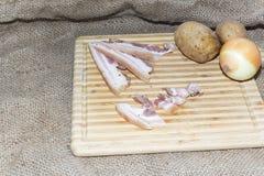 Amincissez le lard de coupe sur un conseil en bois Images libres de droits