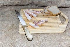 Amincissez le lard de coupe sur un conseil en bois avec un couteau Images stock
