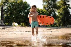 Amincissez le maître nageur aux cheveux longs de plage courant dans l'eau avec la vie-savi Photo stock