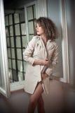 Amincissez le manteau blanc de port de jeune mannequin dans le châssis de fenêtre Belle femme à la mode sexy avec les cheveux bou Photographie stock libre de droits