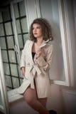 Amincissez le manteau blanc de port de jeune mannequin dans le châssis de fenêtre Belle femme à la mode sexy avec les cheveux bou Photo stock