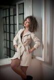 Amincissez le manteau blanc de port de jeune mannequin dans le châssis de fenêtre Belle femme à la mode sexy avec les cheveux bou Image libre de droits