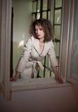 Amincissez le manteau blanc de port de jeune mannequin dans le châssis de fenêtre Belle femme à la mode sexy avec les cheveux bou Photo libre de droits