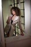 Amincissez le manteau blanc de port de jeune mannequin dans le châssis de fenêtre Belle femme à la mode sexy avec les cheveux bou Photographie stock