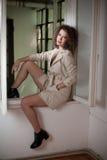 Amincissez le manteau blanc de port de jeune mannequin dans le châssis de fenêtre Belle femme à la mode sexy avec les cheveux bou Photos stock