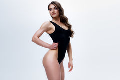 Amincissez le modèle femelle dans une combinaison noire sur le fond blanc Photo libre de droits