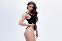 Amincissez le modèle femelle dans une combinaison noire sur le fond blanc Photographie stock libre de droits